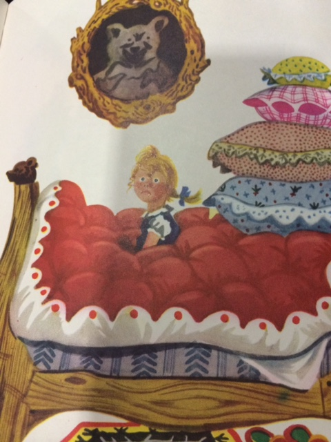 Illustration from a children's book shows a little girl sitting on a bed piled high with quilts and pillows